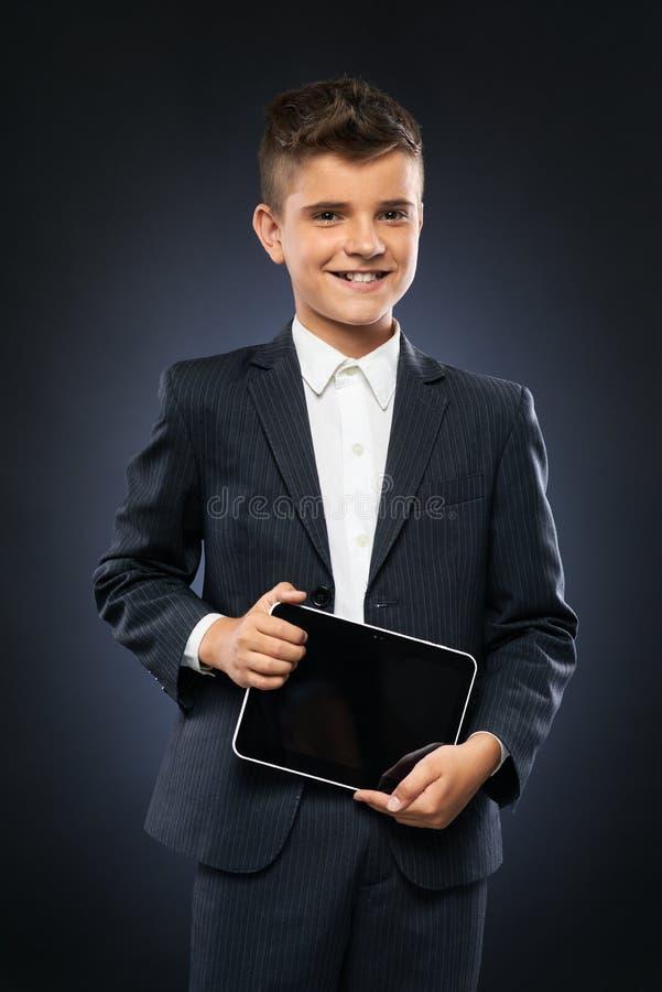 Junge im schwarzen Anzug, der eine Tablette hält stockfotografie