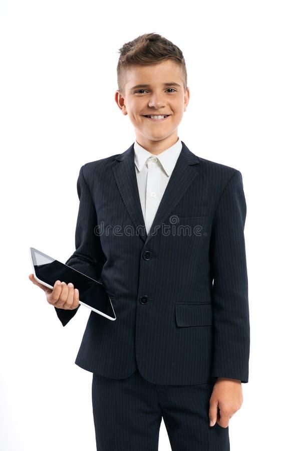 Junge im schwarzen Anzug, der einen Tablet-Computer hält lizenzfreies stockbild