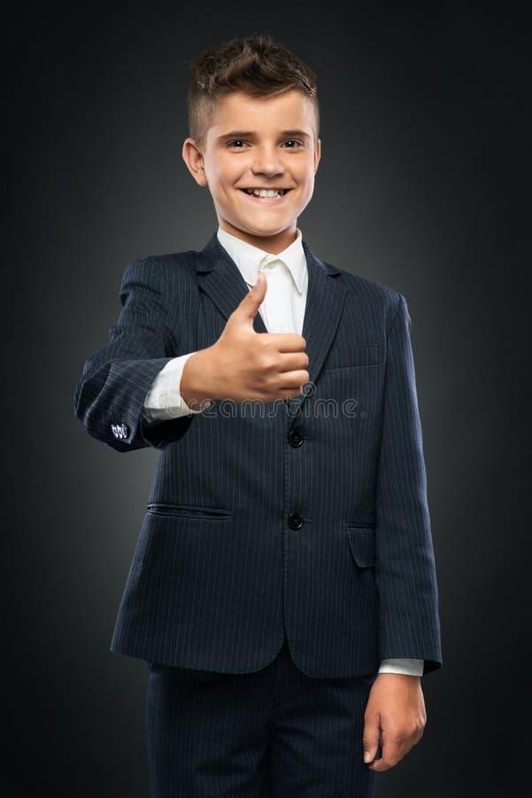 Junge im schwarzen Anzug, der sich Daumen zeigt stockfotografie