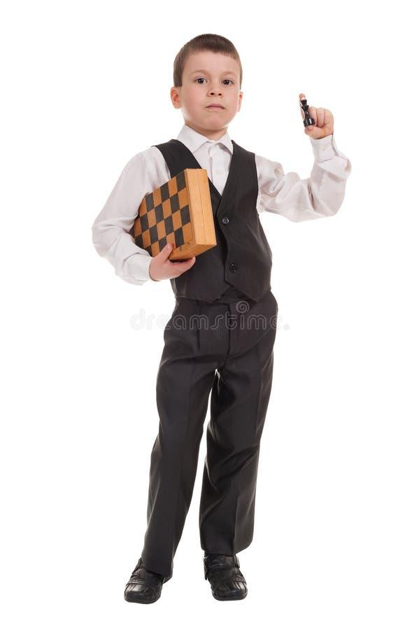 Junge im schwarzen Anzug mit Schach lizenzfreies stockfoto