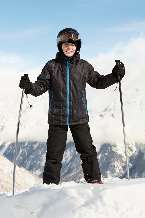 Junge im Skianzug steht, lehnend auf Skipolen lizenzfreie stockbilder