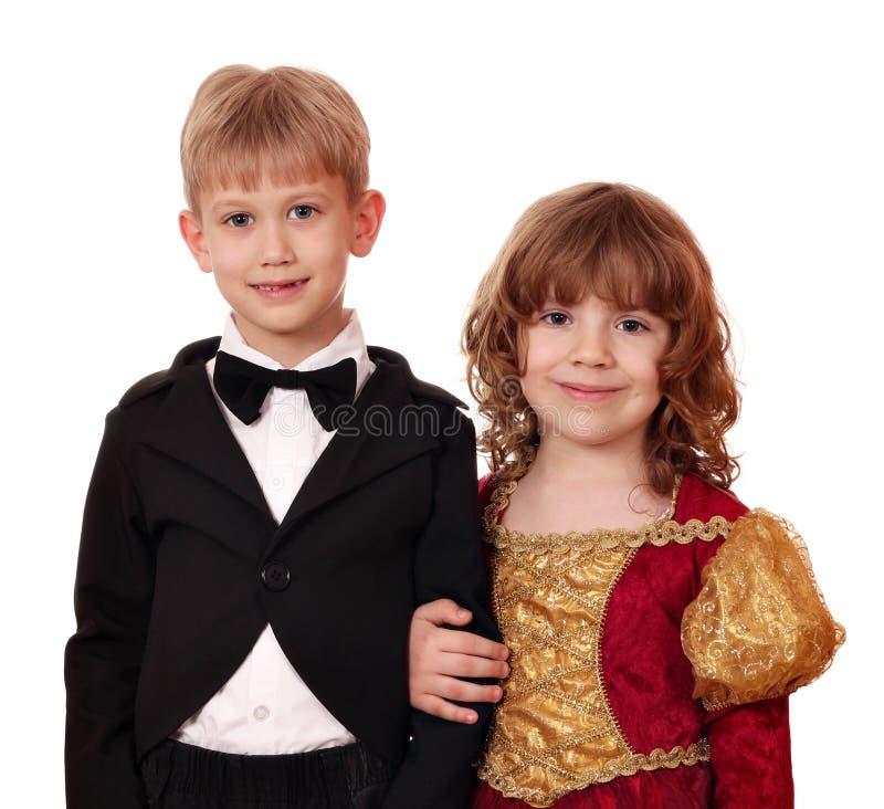 Junge im Smoking und im kleinen Mädchen im goldenen Kleid lizenzfreies stockbild
