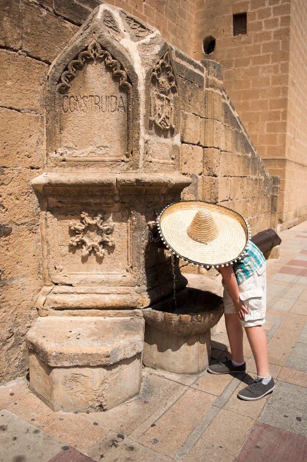 Junge im Sombrero trinkend vom Brunnen stockfoto