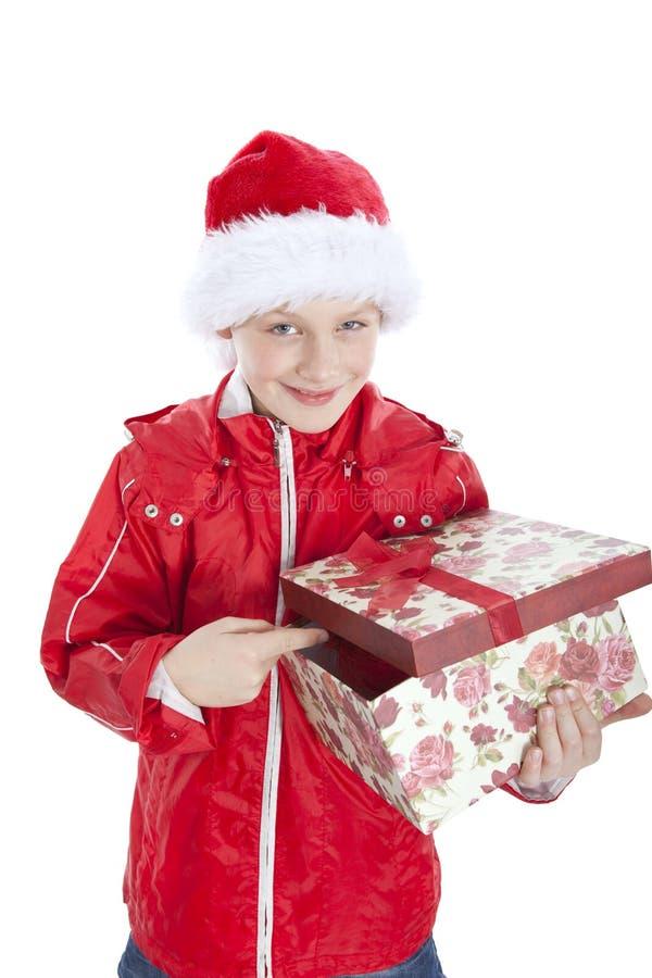 Junge im Weihnachtshut, der anwesenden Überwhit anhält stockbild