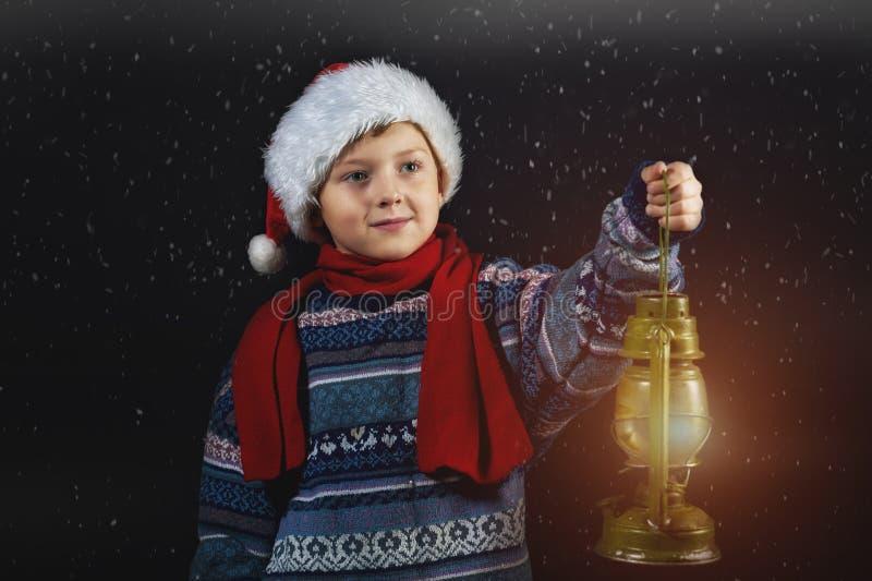 Junge im Weihnachtshut mit einer Laterne in seiner Hand lizenzfreies stockfoto