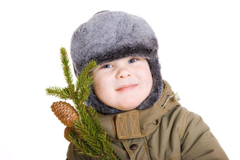 Junge im Wintermantel mit einem Zweig des Pelzbaums stockbild