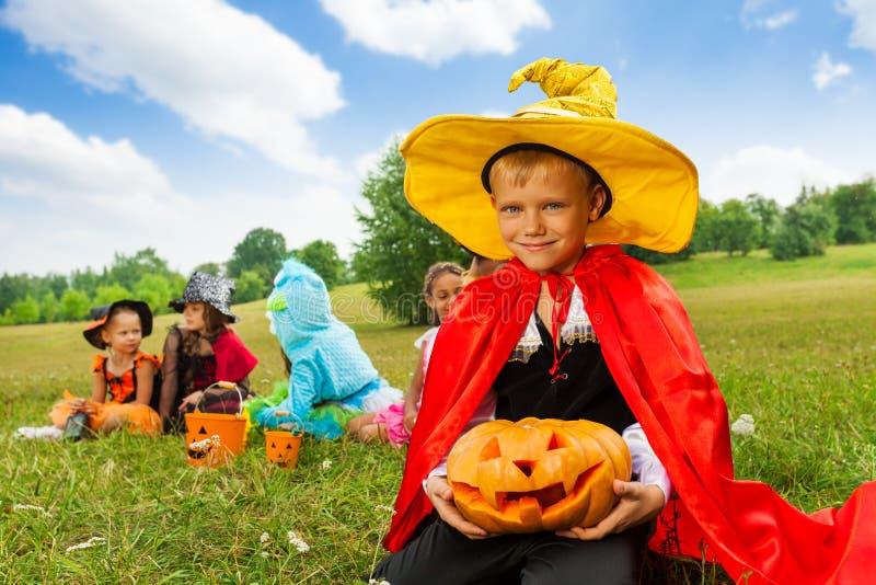 Junge im Zaubererkostüm hält Halloween-Kürbis stockfotos