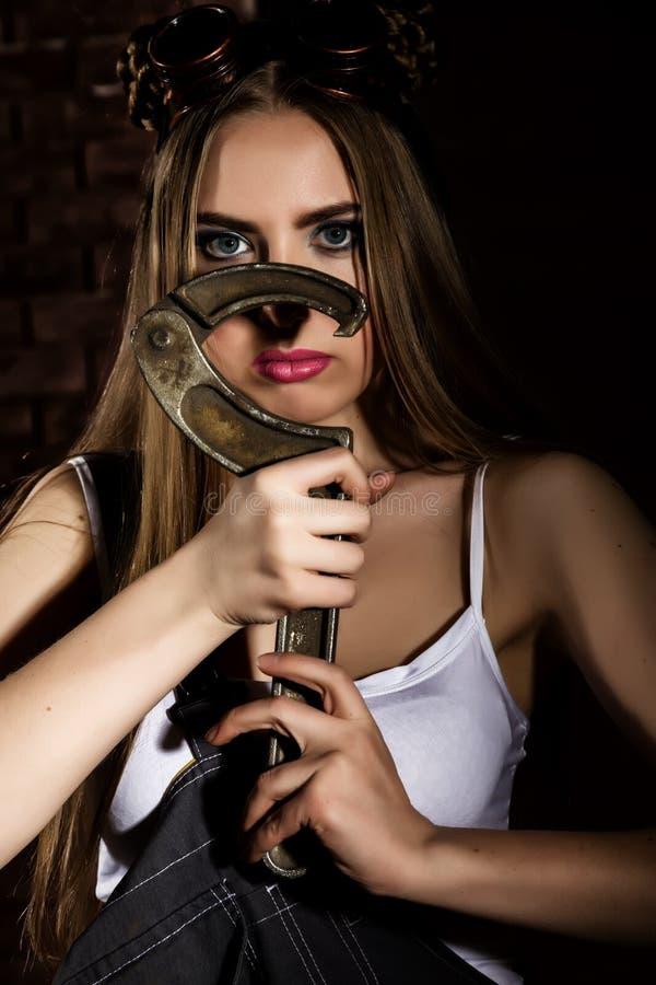 Junge impulsive sexy Frau gekleidet als Automechaniker und schweißenden Gläser, die einen großen Schlüssel halten lizenzfreies stockfoto