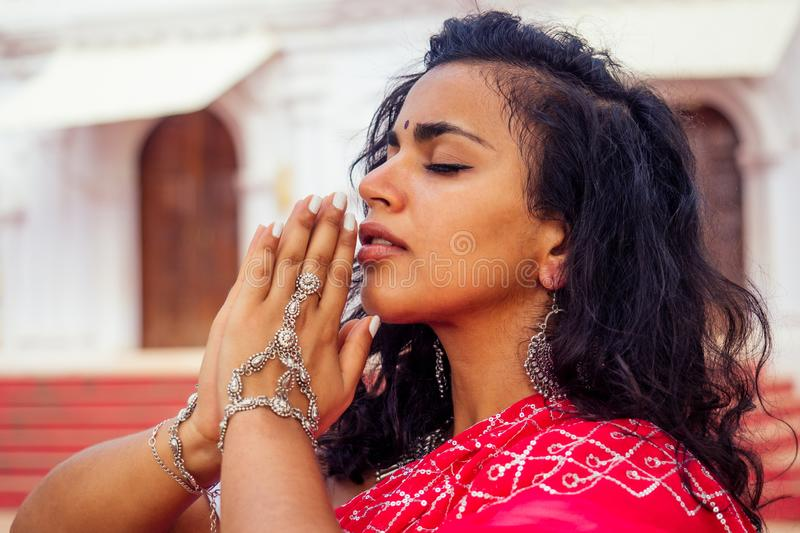 Junge indische Frau in traditionellem sari roten Kleid beten in einem hinteren Tempel goa india Hinduismus Namensfrau stockfotos