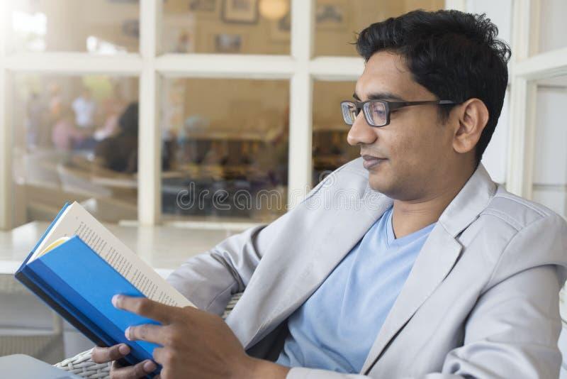 Junge indische männliche Lesung stockfotos