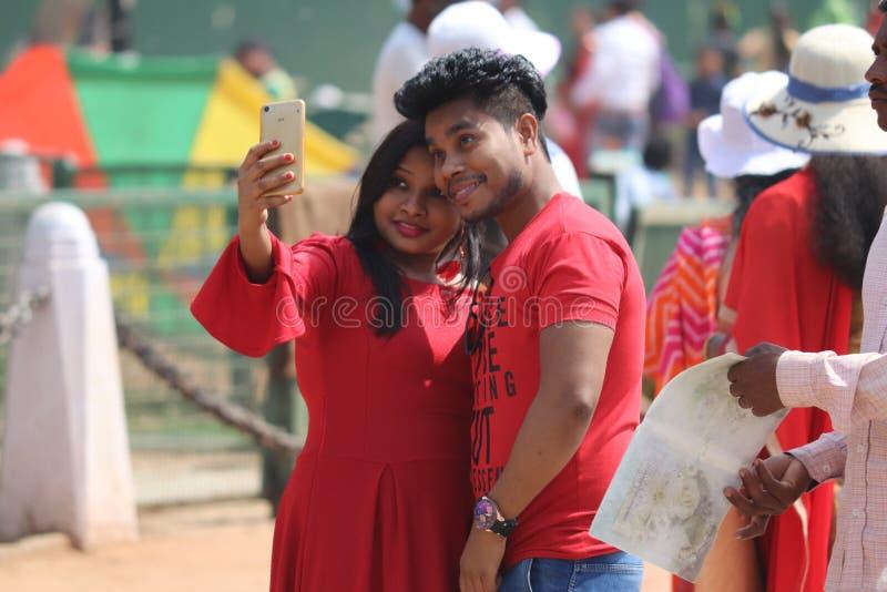 Junge indische Paare, die selfie auf Straßen von Neu-Delhi, Indien nehmen lizenzfreie stockfotografie