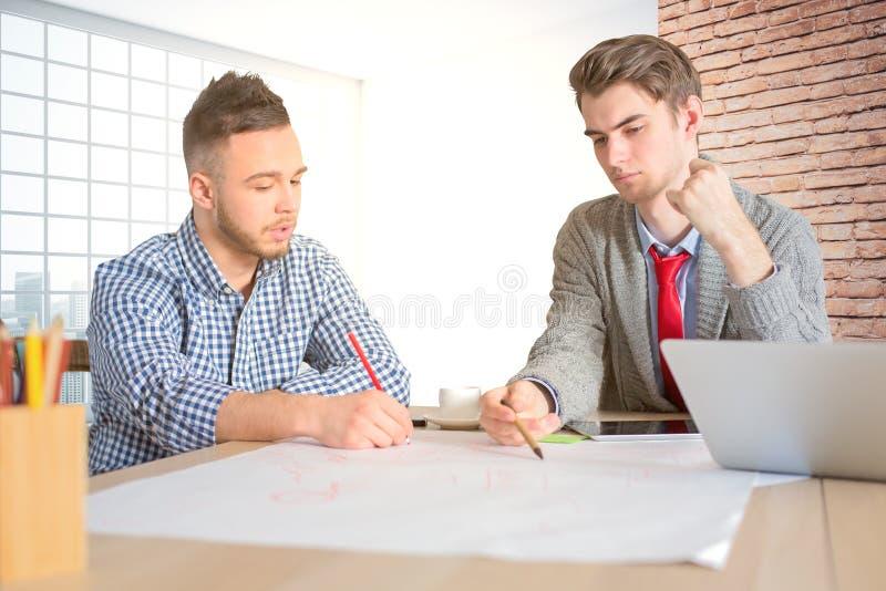 Junge Ingenieure am Arbeitsplatz lizenzfreie stockbilder