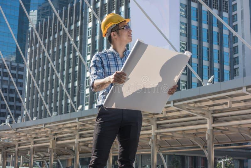 Junge Ingenieure, die Pläne in der Stadt betrachten lizenzfreie stockfotos