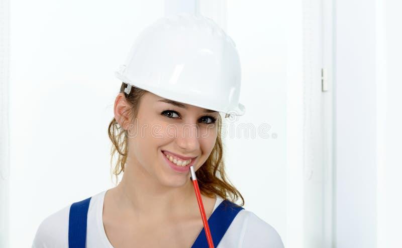 Junge Ingenieurfrau mit weißem Sicherheitsschutzhelm stockfotos