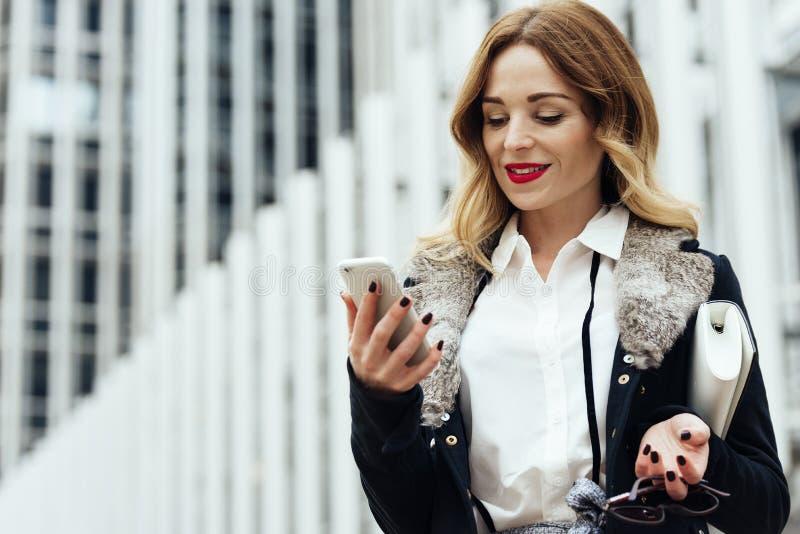 Junge intelligente Berufsfrauenlesung unter Verwendung des Telefons stockfotografie