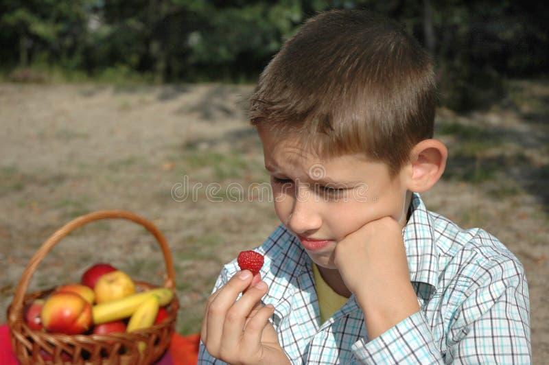 Junge isst Himbeere stockfoto