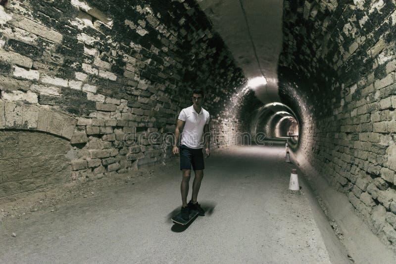 Junge 20-25 Jahre alte Mann im Tunnel mit Skateboard Umgebendes lig stockbild