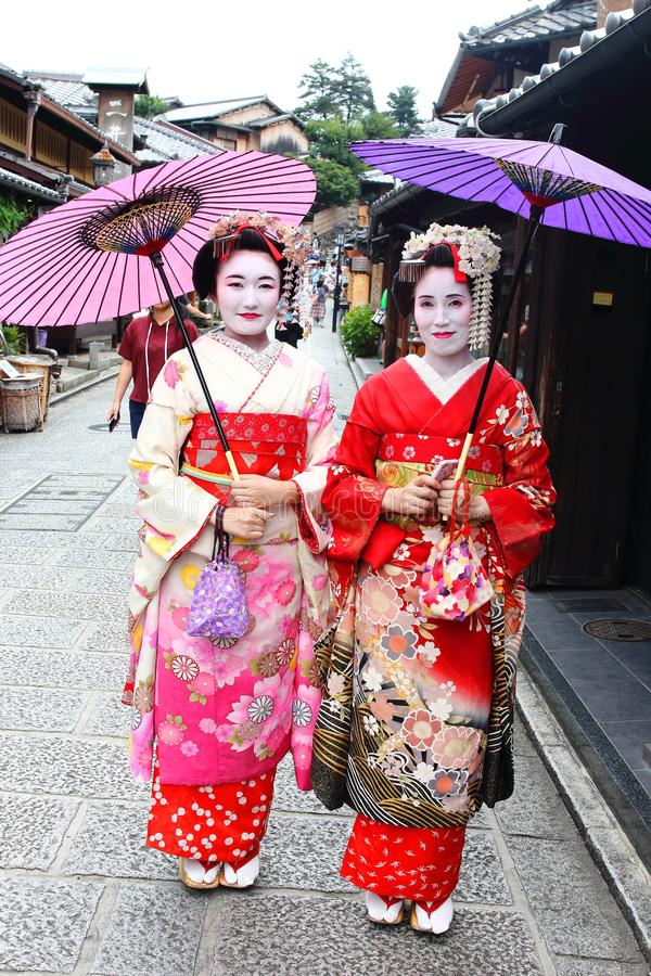 Junge japanische Mädchen kleideten in Geisha ` s Gewohnheit an, die einen Spaziergang in den Stein-gepflasterten Straßen von Nine lizenzfreie stockfotos