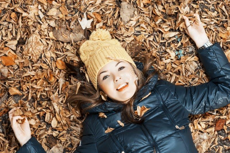 Junge Jugendliche, die im Herbstlaub liegt lizenzfreie stockfotos