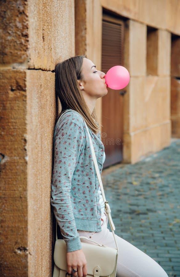Junge Jugendliche, die rosa Kaugummi durchbrennt lizenzfreie stockbilder