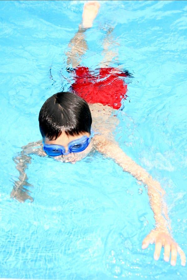 Junge Junge Swims lizenzfreie stockbilder