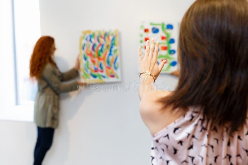 Junge Künstler in hängender Malerei der Galerie auf Wänden lizenzfreie stockfotos