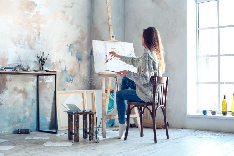 Junge Künstlerin, die zu Hause kreative malende hintere Ansicht malt stockfotografie