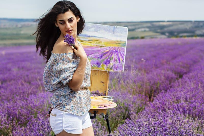 Junge Künstlermalerei auf dem Lavendelgebiet stockbilder
