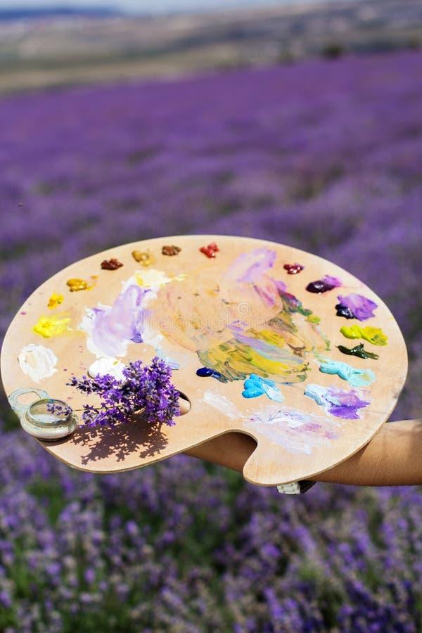 Junge Künstlermalerei auf dem Lavendelgebiet lizenzfreie stockbilder