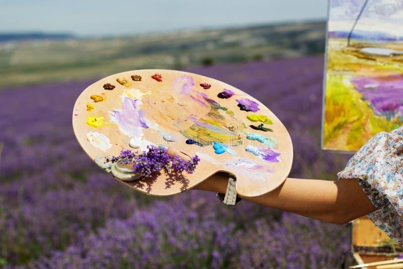 Junge Künstlermalerei auf dem Lavendelgebiet stockbild