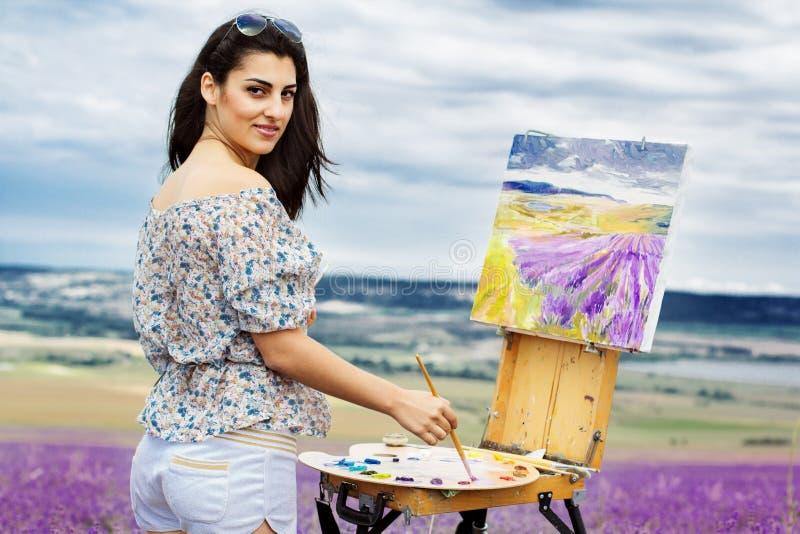 Junge Künstlermalerei auf dem Lavendelgebiet lizenzfreies stockfoto