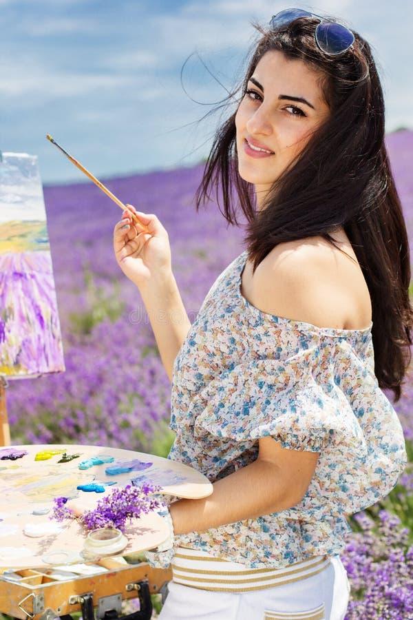 Junge Künstlermalerei auf dem Lavendelgebiet stockfotos