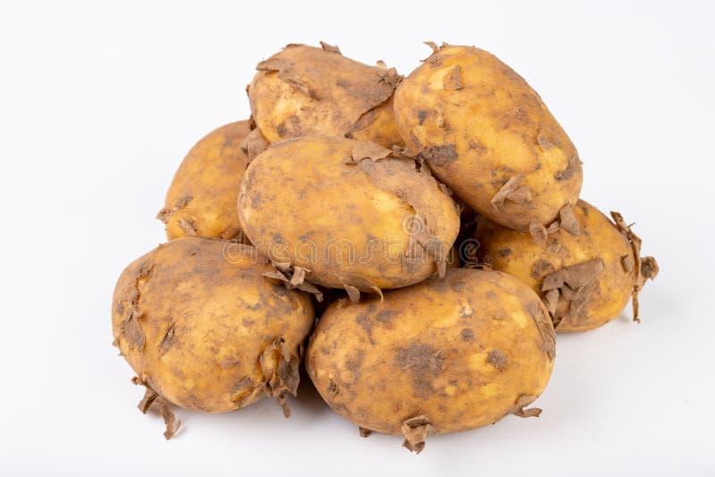Junge Kartoffeln auf einem weißen Küchentisch Gemüse vorbereitet für das Säubern stockbilder