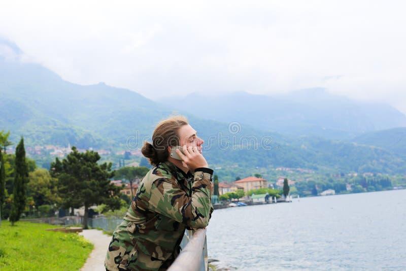 Junge Kaukasier, die mit Smartphone in der Nähe von Banister, See Como und Alpen im Hintergrund sprechen stockfotografie
