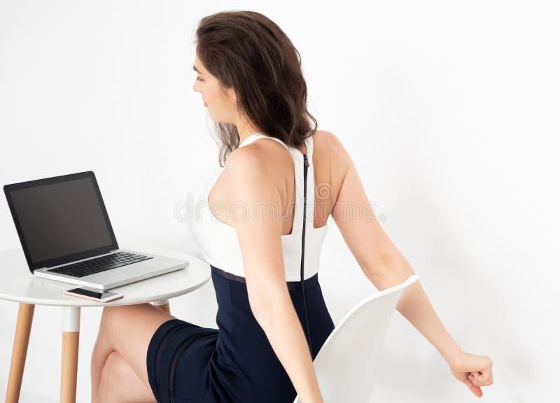 Junge kaukasische Arbeitsgeschäftsfrau auf Schreibtisch mit dem Laptop, der einige Übungen ausdehnt, um eine Pause von der Arbeit lizenzfreie stockfotografie