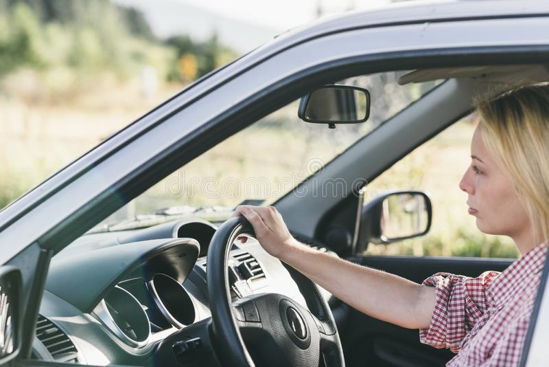 Junge kaukasische blonde Frau, die mit dem Auto reist und Spaß auf ihrer Sommerferienreise hat Glückliches Mädchen, das Auto auf  stockbild