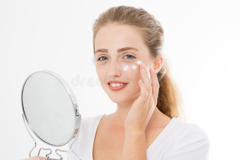 Junge kaukasische Blondine mit Spiegel und Gesichtshautpflegefeuchtigkeitscreme auf dem Gesicht lokalisiert auf weißem Hintergrun stockbild