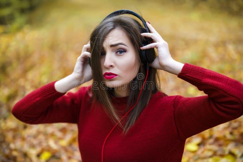 Junge kaukasische Brunettefrau mit Kopfhörern draußen auf autum stockfotografie