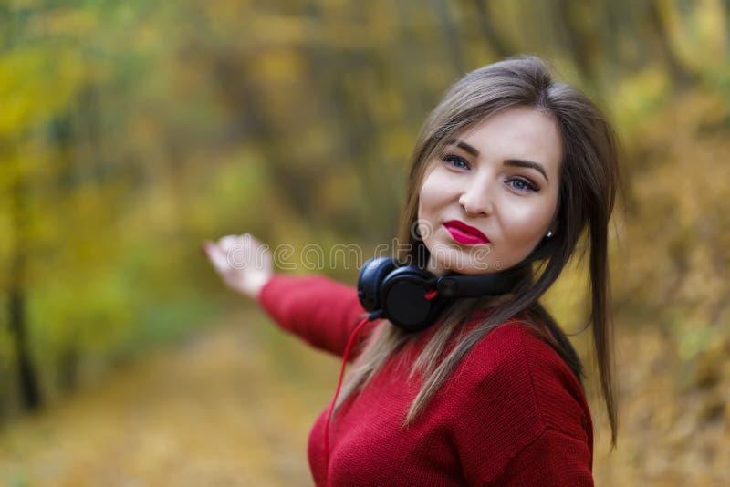 Junge kaukasische Brunettefrau mit Kopfhörern draußen auf autum stockbild