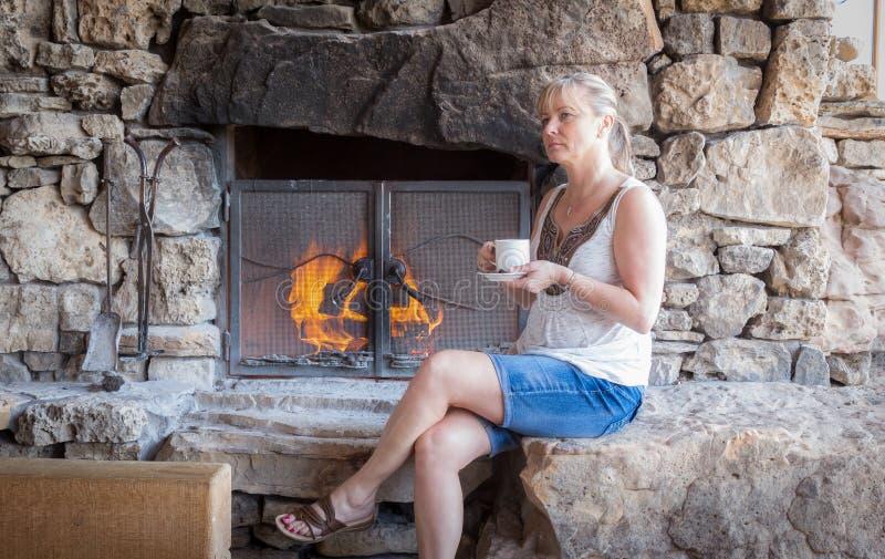 Junge kaukasische Frau, die auf dem Herd durch ein Feuer und einen trinkenden Kaffee sitzt lizenzfreies stockbild
