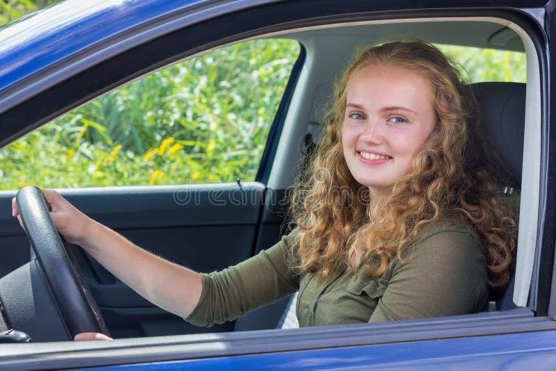 Junge kaukasische Frau, die Auto fährt stockbild