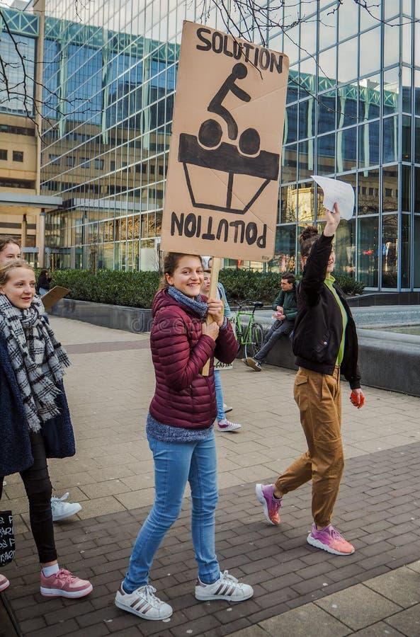 Junge kaukasische Frau, die eine handgemachte Fahne mit Slogan während eines Schulstreiks hält lizenzfreies stockbild
