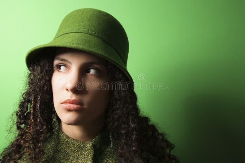 Junge kaukasische Frau, die grüne Kleidung und Hut trägt. lizenzfreie stockbilder