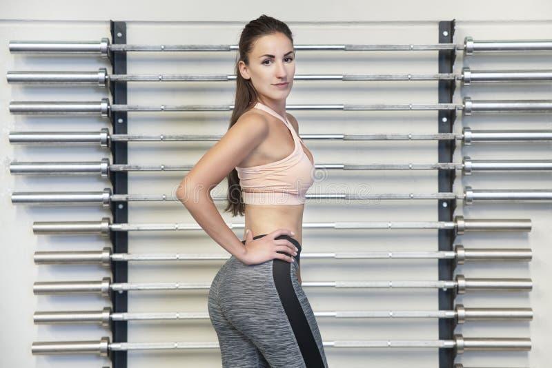 Junge kaukasische Frau, die im Fitnessstudio oder im Fitnessstudio ihre schöne Physik zeigt stockbilder