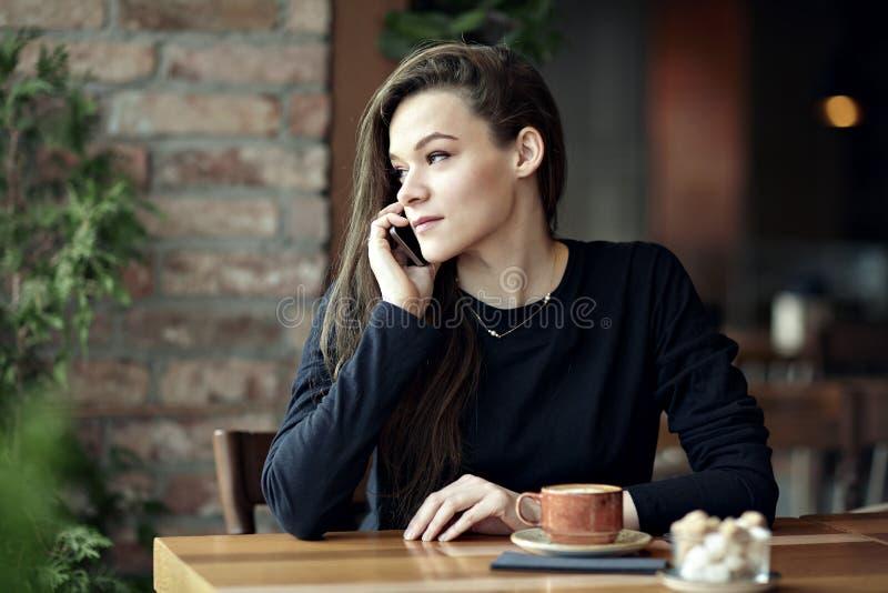 Junge kaukasische Frau, die telefonisch in einem Restaurant spricht Die goldene Taste oder Erreichen für den Himmel zum Eigenheim stockfotografie
