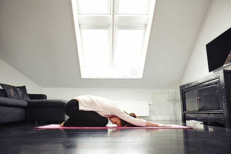 Junge kaukasische Frau, die Yoga im Wohnzimmer ausübt stockbilder
