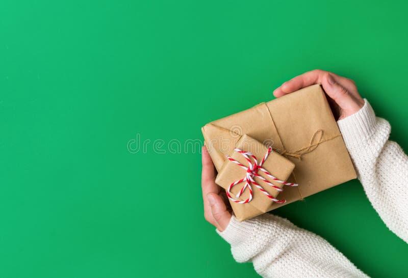 Junge kaukasische Frau in gestrickter weißer Strickjacke hält in der Hand Stapel Geschenkboxen, die im braunen Kraftpapier auf gr lizenzfreie stockbilder