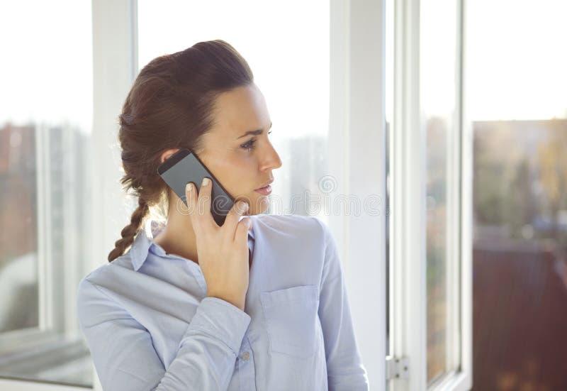 Junge kaukasische Frau im Büro unter Verwendung des Telefons stockfotos