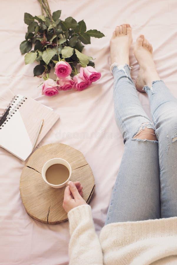Junge kaukasische Frau im Bett früh morgens, beunruhigte Jeans und eine weiße Strickjacke und Griffe ein Tasse Kaffee tragend Ros lizenzfreies stockbild