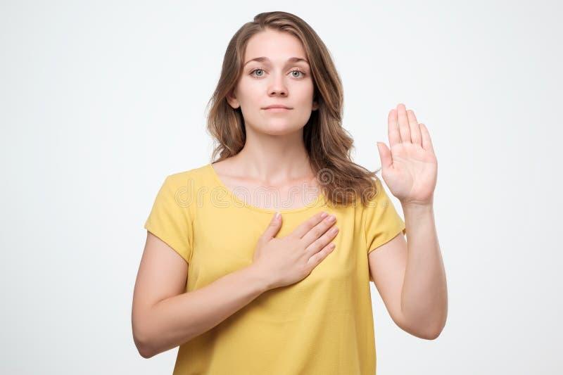 Junge kaukasische Frau im gelben Hemd, das ein Versprechen macht lizenzfreie stockbilder